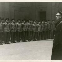 Alumnes uniformats firmes davant d'un oficial al vestíbul de la Escuela Oficial de Náutica. Data aproximada entre 1939-1958 en què el director era Francisco Condeminas Mascaró.