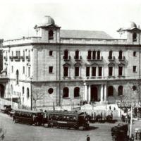 Exterior de la Escuela Oficial de Náutica de Barcelona des de la seva cantonada sud-est. Any 1932, amb carros i tramvia al voltant.