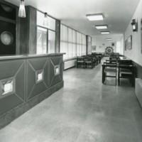 """Interior del bar del """"Club de la Escuela Oficial de Náutica"""", amb la barra de servei a l'esquerra, taules i el timó de decoració a la paret del fons. Barcelona."""