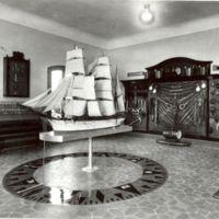 Aula de maniobra de la Escuela Oficial de Náutica amb expositors de materials nàutics i el vaixell Pepito al centre. 1932.