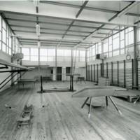 """Interior del gimnàs del """"Club de la Escuela Oficial de Náutica"""" amb espatlleres a la dreta. Barcelona"""