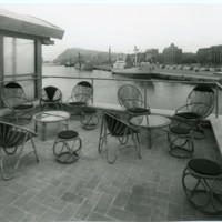 """Terrassa exterior de la sala de professors del """"Club de la Escuela Oficial de Náutica"""" amb taules i cadires de vímet i vistes al Port de Barcelona."""
