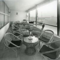 """Terrassa coberta del bar del """"Club de la Escuela Oficial de Náutica"""" amb taules i cadires de vímet i vista parcial del Port de Barcelona."""
