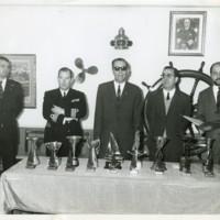 Autoritats darrera de la taula de trofeus de la competició de regatas tipus Vaurien y 470 a punt de la seva entrega al bar del Club de la Escuela Oficial de Náutica de Barcelona. 1969